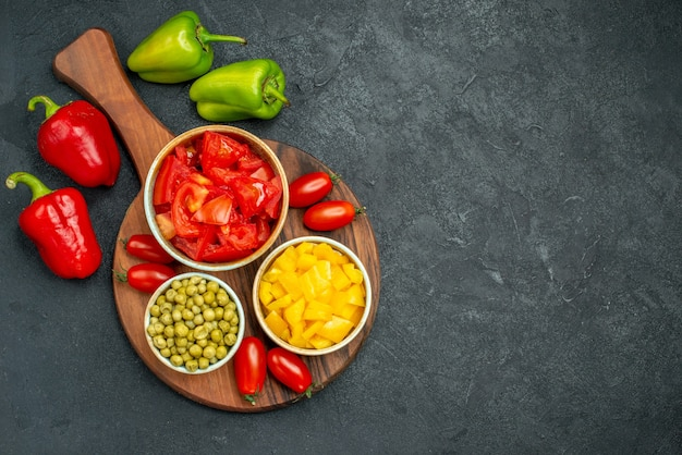 Vista superior de cuencos de verduras en el soporte del plato con verduras en el lateral y espacio libre para el texto sobre fondo gris oscuro