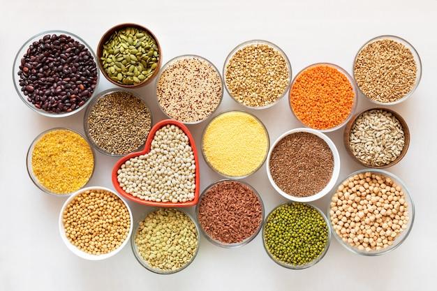 Vista superior de cuencos de vidrio con cereales, frijoles y semillas. Foto Premium
