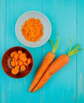 Vista superior de cuencos con zanahoria rallada y rallada y zanahorias enteras sobre fondo azul.