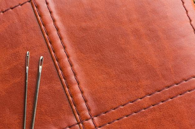 Vista superior de cuero con agujas y espacio de copia.