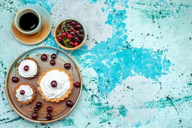 Vista superior de cupcake con cerezas y taza de café americano