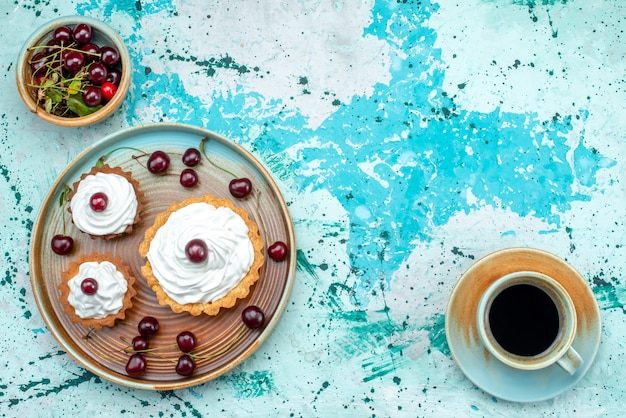 Vista superior de cupcake con crema y cerezas en la parte superior junto a una taza de café americano