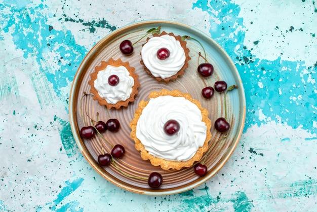 Vista superior de cupcakes con cerezas y crema en azul claro,