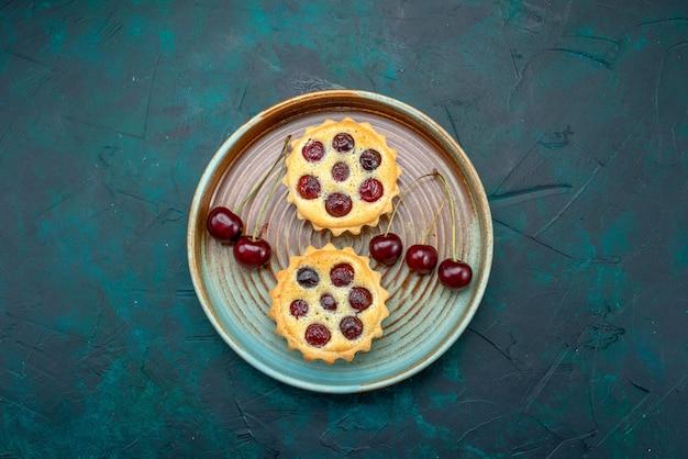 Vista superior de cupcakes con cerezas frescas en placa