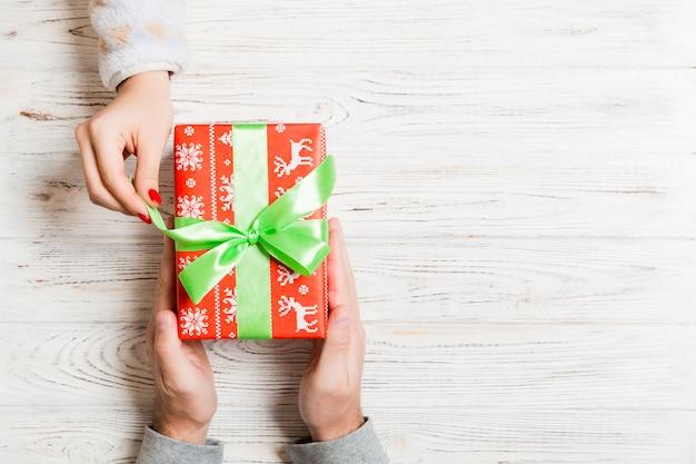 Vista superior dando y recibiendo un regalo en madera. presente en manos masculinas y femeninas. amor . copyspace