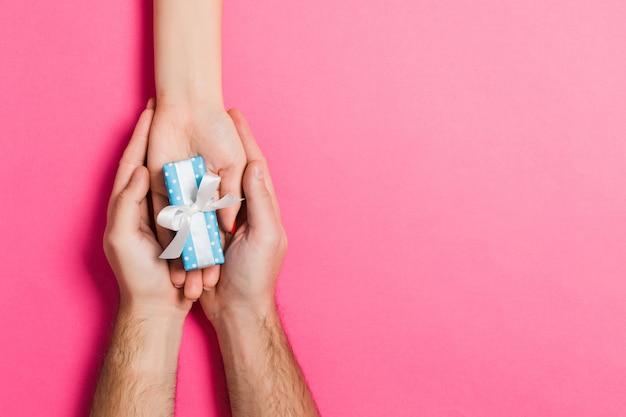 Vista superior de dar y recibir un regalo sobre fondo colful. un hombre y una mujer con regalo en las manos.