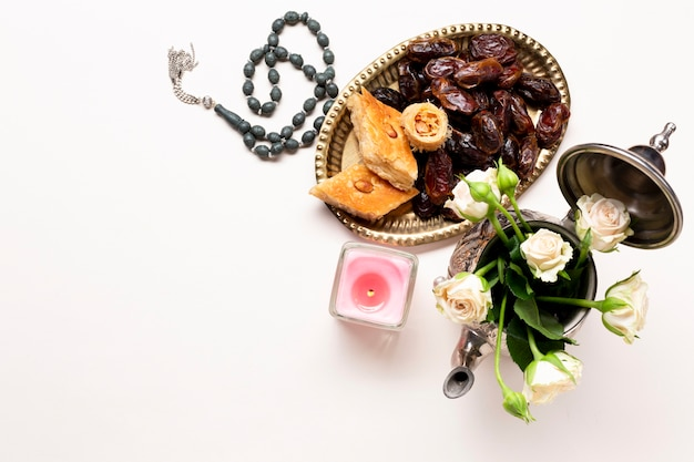 Vista superior de dátiles secos con rosas y velas.