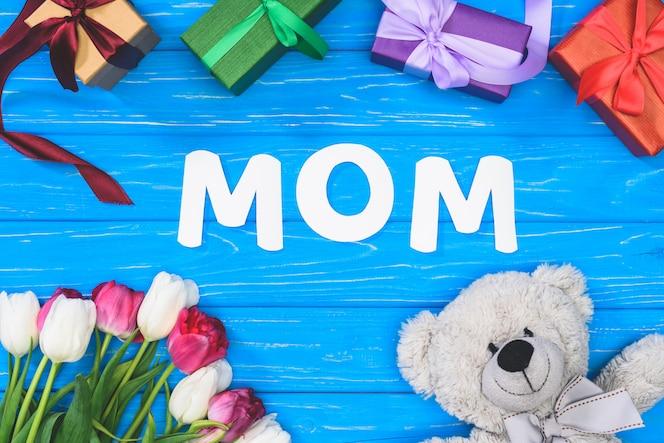 Vista superior de cajas de regalo, oso de peluche, tulipanes y mamá de la palabra en la tabla azul, concepto de día de las madres