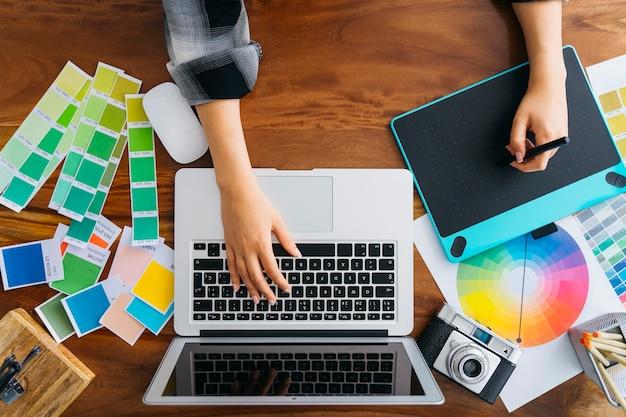 Vista superior de diseñadora gráfica trabajando con tableta gráfica y portátil