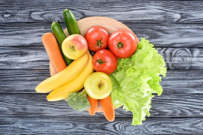 Vista superior de frutas y verduras maduras frescas en la placa en la mesa de madera