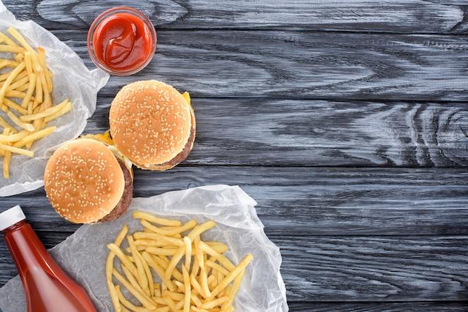 Vista superior de hamburguesas con papas fritas y salsa de tomate en la mesa de madera