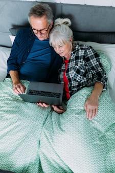 Vista superior de pareja mayor en cama con portátil