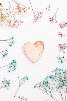 Vista superior decoración con forma de corazón y flores.