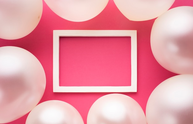 Vista superior decoración con globos, marco y fondo rosa