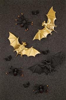 Vista superior de la decoración de halloween con murciélagos de plástico negro y dorado sobre brillo