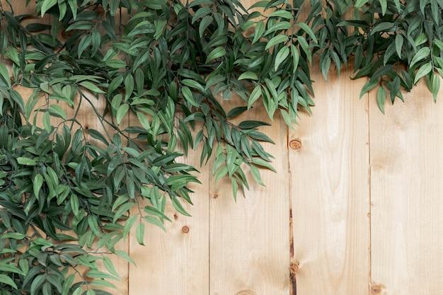 Vista superior decoración con hojas sobre fondo de madera