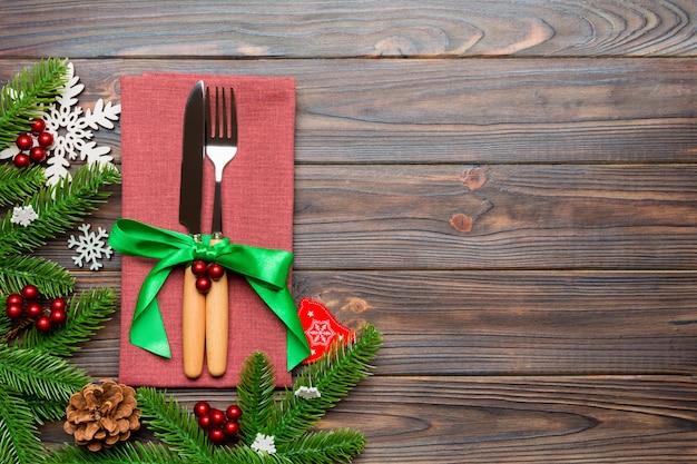 Vista superior de decoraciones de navidad sobre fondo de madera. tenedor y cuchillo en servilleta atados con cinta y espacio vacío.