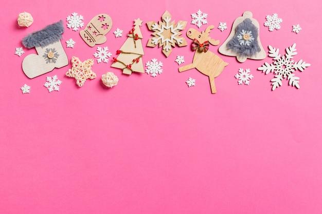 Vista superior de decoraciones navideñas y juguetes sobre fondo rosa. concepto de adorno navideño con espacio vacío para su diseño