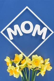 Vista superior del ramo de narcisos y madre de la palabra en el marco aislado en azul, conce del día de madres