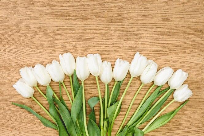 Vista superior del ramo de tulipanes blancos en la mesa de madera