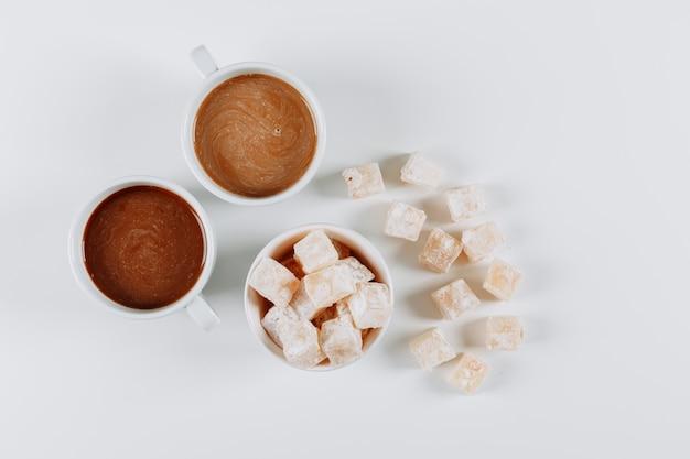 Vista superior delicias turcas lokums en cuencos, con café sobre fondo blanco. horizontal