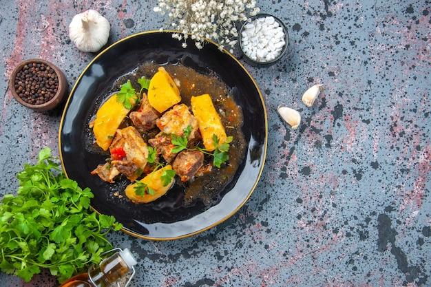 Vista superior de la deliciosa cena con patatas de carne servidas con verde en un plato negro y especias de ajo botella de aceite caído sobre fondo de colores de mezcla
