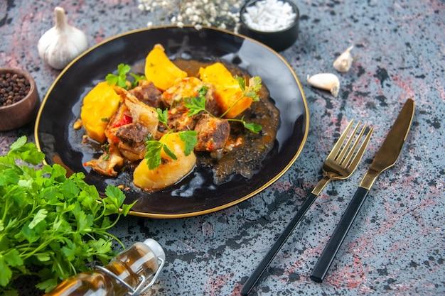 Vista superior de la deliciosa cena con patatas de carne servidas con verde en un plato negro y especias de ajo cubiertos de flores de botella de aceite caído en fondo de colores mezclados