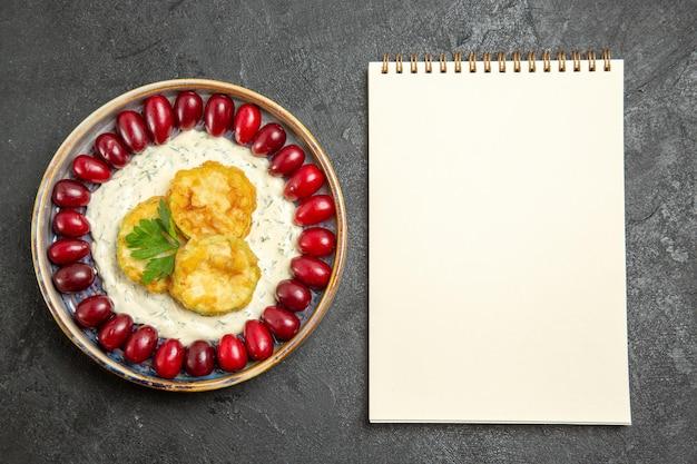 Vista superior de la deliciosa comida de calabaza con cornejos rojos frescos en la superficie gris