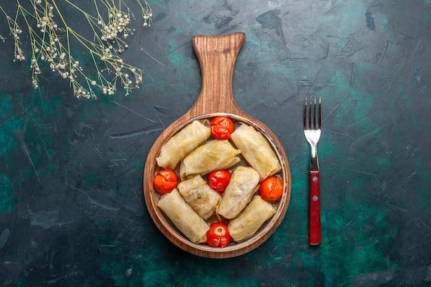 Vista superior deliciosa comida de carne de dolma enrollada con repollo y tomates en el escritorio azul oscuro carne comida cena verduras plato cocina