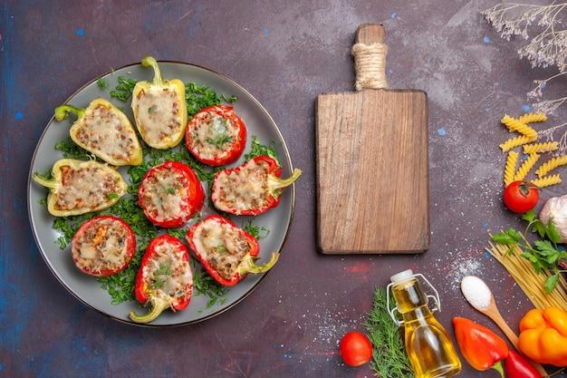 Vista superior de deliciosa comida de pimientos horneados con carne en el interior y verduras en el escritorio oscuro, cena, plato, comida, hornear