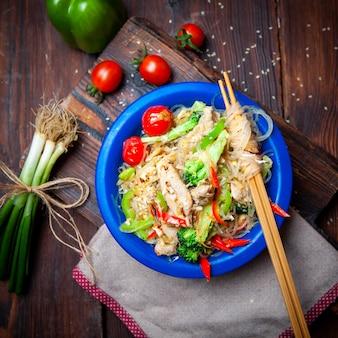 Vista superior deliciosa comida en placa azul con cebollas verdes, tomates y palillos sobre fondo de madera oscura.