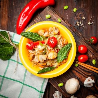 Vista superior deliciosa comida en plato amarillo con pimiento rojo, tomates en madera, tela y fondo de madera oscura.
