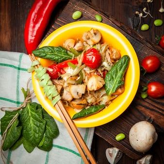 Vista superior deliciosa comida en plato amarillo con pimiento rojo, tomates, palillos en madera, tela y fondo de madera oscura.