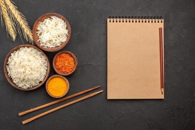 Vista superior deliciosa comida sabrosa llana de arroz cocido dentro de la placa en el espacio oscuro
