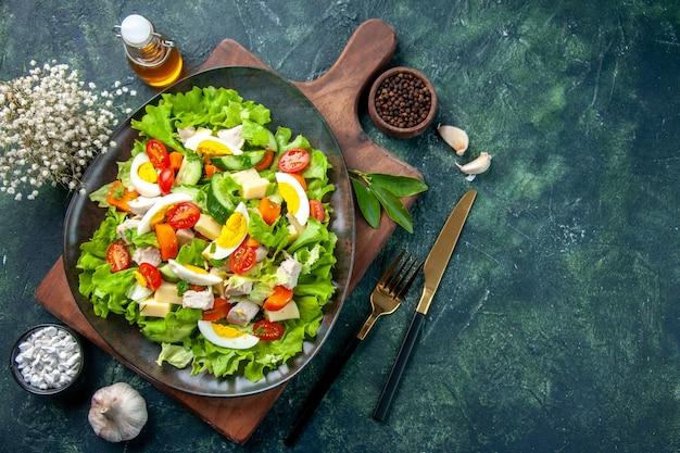 Vista superior de la deliciosa ensalada con ingredientes frescos en la tabla de cortar de madera, especias, botella de aceite, ajos, cubiertos, sobre fondo negro de colores de mezcla