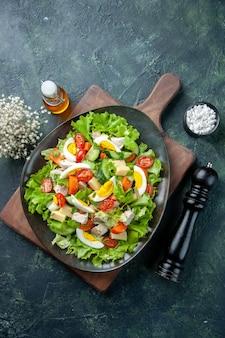 Vista superior de la deliciosa ensalada con muchos ingredientes frescos en la botella de aceite de sal de tabla de cortar de madera sobre fondo de colores mezcla verde negro