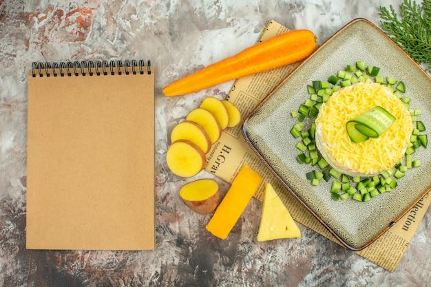 Vista superior de una deliciosa ensalada en un periódico viejo y dos tipos de queso y zanahorias, papas picadas, cuaderno en mesa de colores mezclados