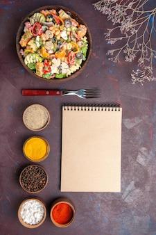 Vista superior deliciosa ensalada de verduras con diferentes condimentos sobre fondo oscuro dieta saludable ensalada de verduras almuerzo