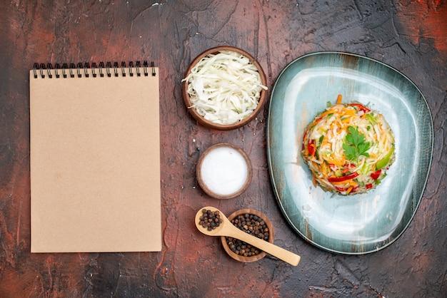 Vista superior deliciosa ensalada de verduras con repollo en rodajas sobre fondo oscuro color maduro vida sana foto comida comida