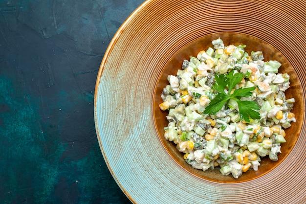 Vista superior de una deliciosa ensalada con verduras en rodajas dentro de la placa en el escritorio azul oscuro.