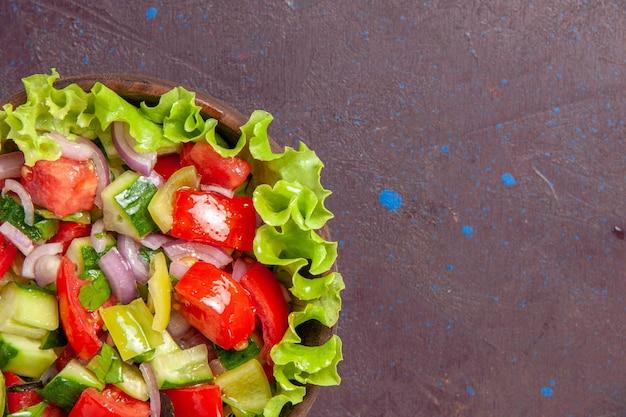 Vista superior de la deliciosa ensalada de verduras en rodajas con ingredientes frescos en el espacio oscuro