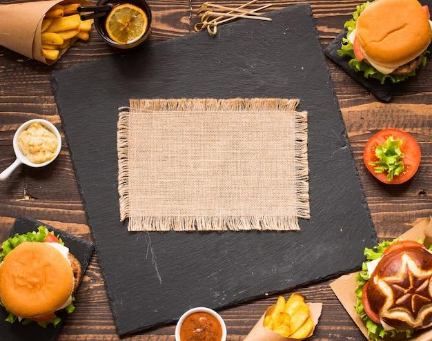 Vista superior de deliciosa hamburguesa, con verduras sobre un fondo de madera.