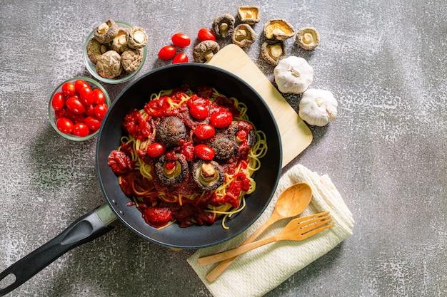 Vista superior de la deliciosa pasta a la boloñesa en una sartén cerca de los ingredientes