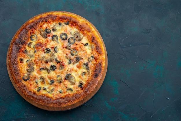 Vista superior de la deliciosa pizza cocida con queso y aceitunas en el escritorio azul oscuro