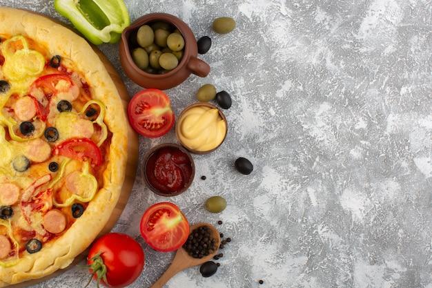Vista superior de la deliciosa pizza con queso con aceitunas, salchichas y tomates rojos sobre el fondo gris masa italiana de comida rápida