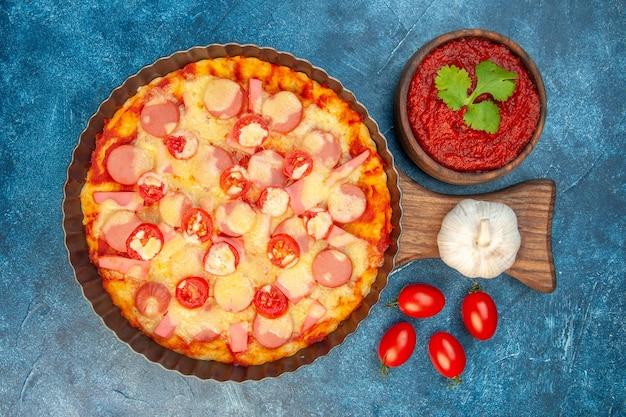 Vista superior de la deliciosa pizza de queso con salchichas y tomates sobre fondo azul, comida italiana, pastel de masa, comida rápida, color fotográfico