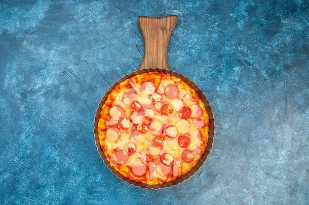 Vista superior deliciosa pizza de queso con salchichas y tomates sobre fondo azul comida masa pastel color comida rápida italiana foto