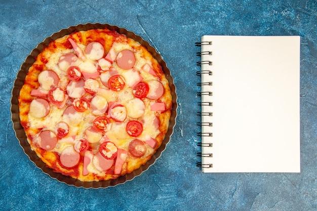 Vista superior de una deliciosa pizza de queso con salchichas y tomates sobre fondo azul, ensalada, comida, pastel, fotografía en color, comida rápida