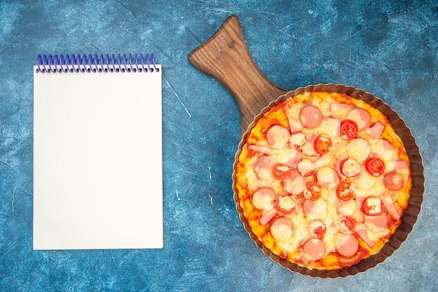 Vista superior deliciosa pizza de queso con salchichas y tomates sobre fondo azul masa pastel color comida rápida italiana foto