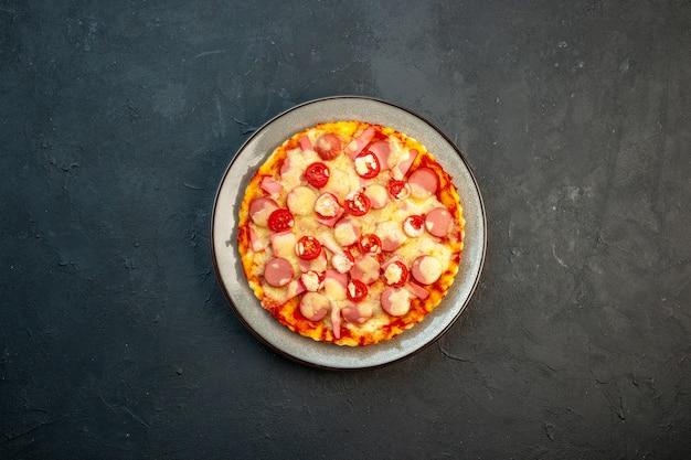 Vista superior de la deliciosa pizza de queso con salchichas y tomates sobre fondo oscuro, comida italiana, pastel de masa, comida rápida, color fotográfico